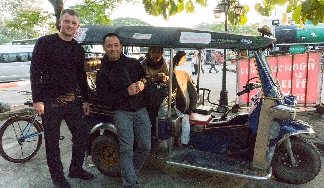 Not posing like tourists next to our tuk tuk.